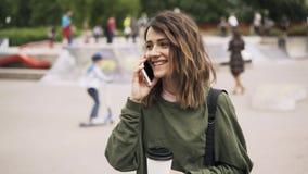 Γυναίκα με τον καφέ στο τηλέφωνο σε ένα skateboard πάρκο απόθεμα βίντεο