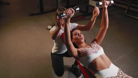 Γυναίκα με τον προσωπικό εκπαιδευτή ικανότητάς της στη γυμναστική που ασκεί με τους αλτήρες φιλμ μικρού μήκους