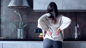 Γυναίκα με τον πόνο στην πλάτη στην κουζίνα απόθεμα βίντεο