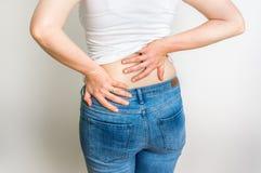 Γυναίκα με τον πόνο στην πλάτη που κρατά την πονώντας πίσω Στοκ Φωτογραφία