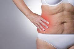 Γυναίκα με τον πόνο στη δεξιά πλευρά του σώματος Πόνος στο ανθρώπινο σώμα στο γκρίζο υπόβαθρο με το κόκκινο σημείο στοκ φωτογραφία