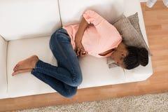 Γυναίκα με τον πόνο στομαχιών που βρίσκεται στον καναπέ στοκ εικόνα