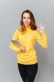 Γυναίκα με τον υπολογιστή ταμπλετών που κλείνει το μάτι και που παρουσιάζει εντάξει σημάδι Στοκ εικόνα με δικαίωμα ελεύθερης χρήσης