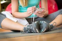Γυναίκα με το έξυπνο τηλέφωνο, που στηρίζεται μετά από τη γυμναστική workout Στοκ Φωτογραφία