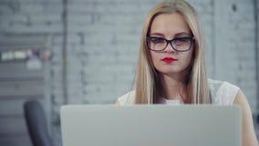 Γυναίκα με το ήρεμο πρόσωπο που λειτουργεί στο σύγχρονο lap-top απόθεμα βίντεο