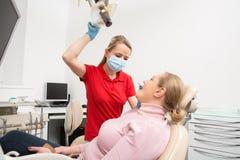 Γυναίκα με το ανοικτό στόμα που έχει τα δόντια της εξετασμένων από τη θηλυκή εξέταση δοντιών οδοντιάτρων στο γραφείο οδοντιάτρων  στοκ φωτογραφία με δικαίωμα ελεύθερης χρήσης