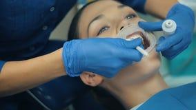Γυναίκα με το λαστιχένιο φράγμα σε ένα στόμα σε έναν οδοντίατρο απόθεμα βίντεο