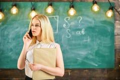 Γυναίκα με το βιβλίο που μιλά στο κινητό τηλέφωνο στην τάξη Δάσκαλος που υποβάλλει έκθεση για τους απόντες σπουδαστές Δάσκαλος συ Στοκ Εικόνες