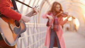 Γυναίκα με το βιολί και άνδρας με τη μουσική παιχνιδιού κιθάρων στην οδό απόθεμα βίντεο