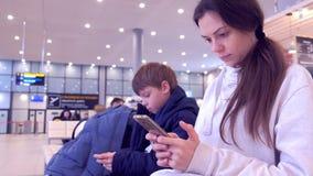 Γυναίκα με το γιο της που κοιτάζει βιαστικά στα κινητά τηλέφωνα στην αίθουσα αερολιμένων που περιμένει την πτήση απόθεμα βίντεο
