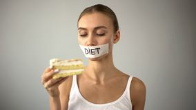 Γυναίκα με το δεμένο με ταινία στόμα που εξετάζει το κέικ, πειρασμός πάλης ναφαγωθεί η πίτα, διατροφή στοκ εικόνες
