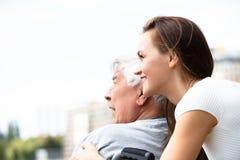 Γυναίκα με το με ειδικές ανάγκες πατέρα της κοντά στο κιγκλίδωμα στοκ εικόνες