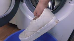 Γυναίκα με το ζευγάρι των άσπρων πάνινων παπουτσιών κοντά στο πλυντήριο απόθεμα βίντεο