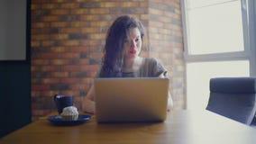 Γυναίκα με το κέικ και τσάι που χρησιμοποιούν το lap-top απόθεμα βίντεο