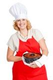 Γυναίκα με το κέικ bundt που φορά μια κόκκινη ποδιά Στοκ Εικόνες