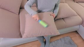 Γυναίκα με το καθαρίζοντας μαξιλάρι ο κυλίνδρων ίνας ο καναπές απόθεμα βίντεο