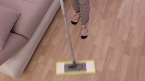 Γυναίκα με το καθαρίζοντας πάτωμα σφουγγαριστρών φιλμ μικρού μήκους