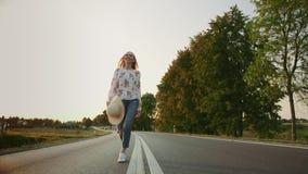 Γυναίκα με το καπέλο που τρέχει στο δρόμο απόθεμα βίντεο