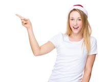 Γυναίκα με το καπέλο Χριστουγέννων και το σημείο δάχτυλων κατά μέρος Στοκ Φωτογραφίες