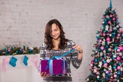 Γυναίκα με το κιβώτιο δώρων κοντά στις διακοσμήσεις Χριστουγέννων Στοκ εικόνες με δικαίωμα ελεύθερης χρήσης