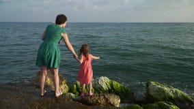Γυναίκα με το κορίτσι στους βράχους στα κύματα απόθεμα βίντεο