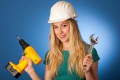 Γυναίκα με το κράνος κατασκευαστών και εργαλεία ευτυχή να κάνουν τη σκληρή εργασία Στοκ Εικόνα