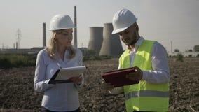 Γυναίκα με το κράνος που σημειώνει στο σημειωματάριό της τη λειτουργώντας έκθεση προόδου του νέου μηχανικού που χρησιμοποιεί το P φιλμ μικρού μήκους