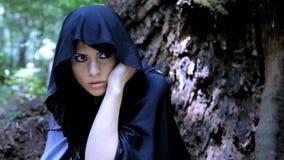 Γυναίκα με το κρύψιμο κουκουλών στο δάσος απόθεμα βίντεο