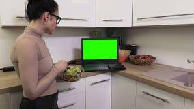Γυναίκα με το κύπελλο των σαλατών κοντά στο PC lap-top με την πράσινη οθόνη απόθεμα βίντεο