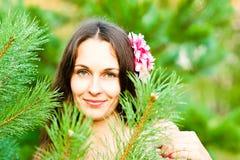 Γυναίκα με το λουλούδι στο τρίχωμά της στοκ φωτογραφία