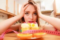 Γυναίκα με το μέτρο και το κέικ ταινιών Δίλημμα διατροφής Στοκ φωτογραφία με δικαίωμα ελεύθερης χρήσης