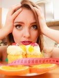 Γυναίκα με το μέτρο και το κέικ ταινιών Δίλημμα διατροφής Στοκ εικόνες με δικαίωμα ελεύθερης χρήσης