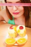 Γυναίκα με το μέτρο και το κέικ ταινιών Δίλημμα διατροφής Στοκ φωτογραφίες με δικαίωμα ελεύθερης χρήσης