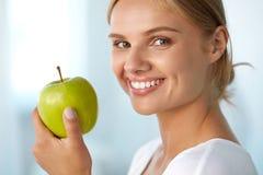 Γυναίκα με το μήλο Όμορφο κορίτσι με το άσπρο χαμόγελο, υγιή δόντια Στοκ φωτογραφία με δικαίωμα ελεύθερης χρήσης