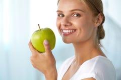 Γυναίκα με το μήλο Όμορφο κορίτσι με το άσπρο χαμόγελο, υγιή δόντια Στοκ Εικόνες