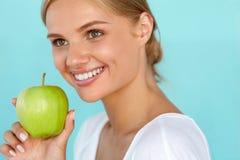 Γυναίκα με το μήλο Όμορφο κορίτσι με το άσπρο χαμόγελο, υγιή δόντια Στοκ εικόνα με δικαίωμα ελεύθερης χρήσης