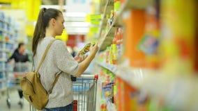 Γυναίκα με το μακρύ σκοτεινό χυμό αγοράς κάρρων τρίχας και αγορών στην υπεραγορά που στέκεται κοντά στο ράφι απόθεμα βίντεο