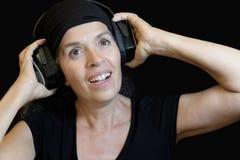 Γυναίκα με το μαύρο υπόβαθρο ακουστικών Στοκ εικόνα με δικαίωμα ελεύθερης χρήσης