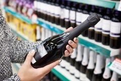 Γυναίκα με το μπουκάλι της σαμπάνιας στο κατάστημα στοκ εικόνα με δικαίωμα ελεύθερης χρήσης