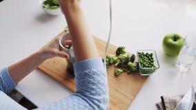 Γυναίκα με το μπλέντερ που μαγειρεύει τα φυτικά τρόφιμα στο σπίτι απόθεμα βίντεο