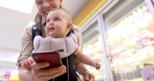 Γυναίκα με το μωρό στο smartphone χρήσεων σφεντονών στο κατάστημα φιλμ μικρού μήκους