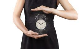 Γυναίκα με το ξυπνητήρι μεταξύ των χεριών, που απομονώνεται σε άσπρο, μαγικών Στοκ εικόνες με δικαίωμα ελεύθερης χρήσης
