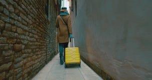 Γυναίκα με το πίσω περπάτημα καροτσακιών κατά μήκος της στενωπού φιλμ μικρού μήκους