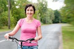 Γυναίκα με το ποδήλατο στο βροχερό Στοκ Φωτογραφία
