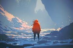 Γυναίκα με το πορτοκαλί θερμό σακάκι που στέκεται στο χειμερινό τοπίο ελεύθερη απεικόνιση δικαιώματος