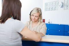 Γυναίκα με το ρεσεψιονίστ στο γραφείο του οδοντιάτρου Στοκ Εικόνες
