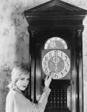 Γυναίκα με το ρολόι παππούδων στα μεσάνυχτα Στοκ φωτογραφία με δικαίωμα ελεύθερης χρήσης