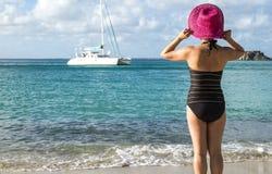 Γυναίκα με το ρόδινο καπέλο αχύρου που εξετάζει ένα καταμαράν στοκ εικόνες