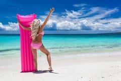 Γυναίκα με το ρόδινο κολυμπώντας στρώμα στην τροπική παραλία στοκ εικόνα με δικαίωμα ελεύθερης χρήσης