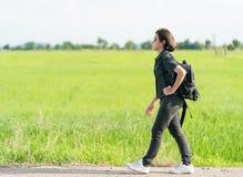 Γυναίκα με το σακίδιο πλάτης που κάνει ωτοστόπ κατά μήκος ενός δρόμου Στοκ Εικόνες